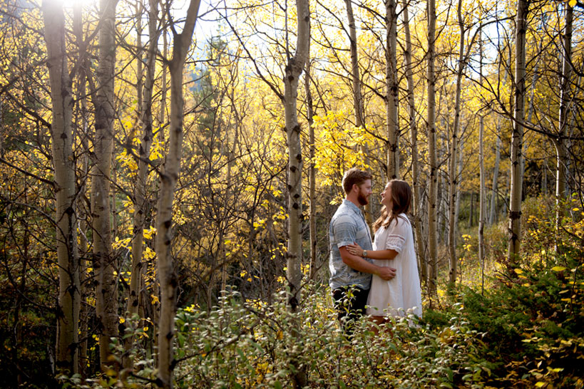 couple in the midst of yellow trees Calgary engagement photography