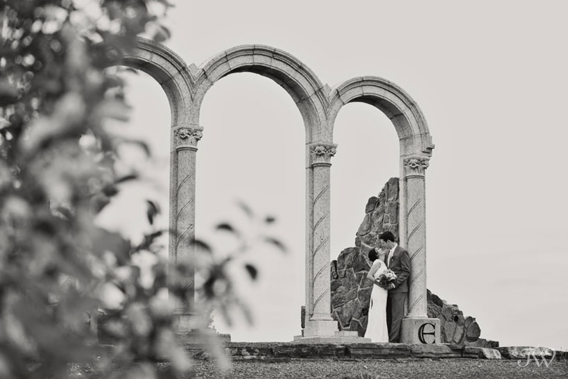 bride and groom pose beneath arches captured by Tara Whittaker Photography