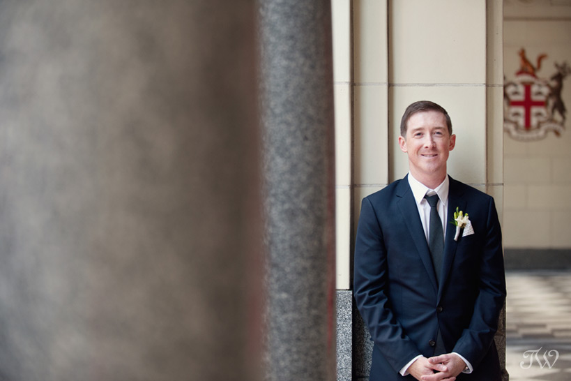 Groom poses on Stephen Avenue captured by Tara Whittaker Photography