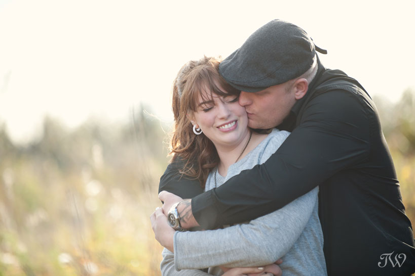 couple snuggle up during their fall engagement photos with Tara Whittaker Photography