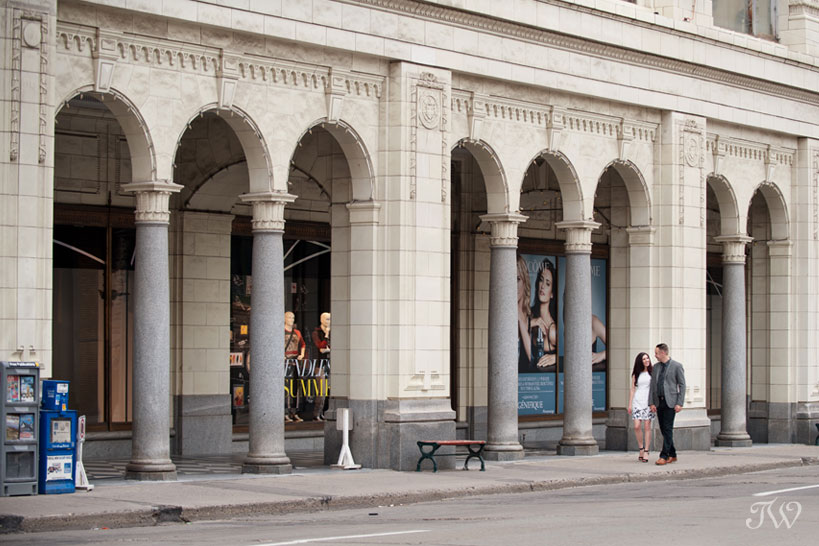 couple stroll past the Hudson Bay arches in downtown Calgary captured by Tara Whittaker Photography
