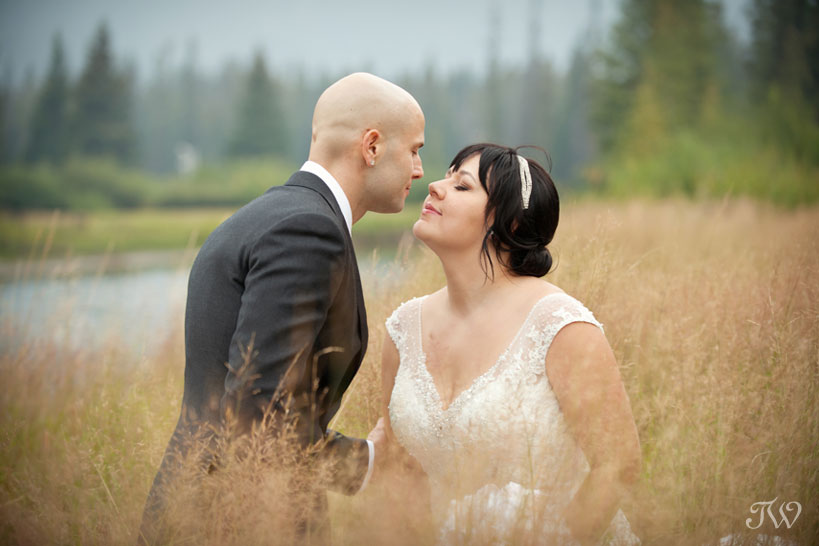 bride and groom by the Bow River in the Town of Banff captured by Tara Whittaker Photography