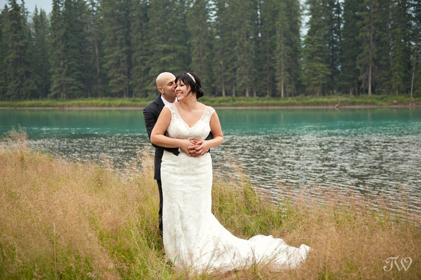 bride and groom pose by the Bow River in Banff captured by Tara Whittaker Photography