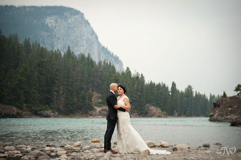 bride and groom by the Bow River in Banff captured by Tara Whittaker Photography