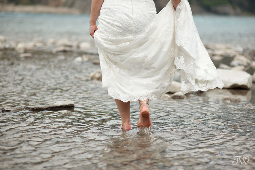 bride wades in the Bow River in the Town of Banff captured by Tara Whittaker Photography