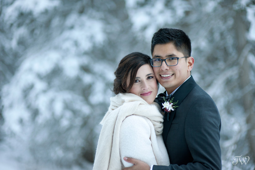 bride and groom pose near snow covered trees captured by Tara Whittaker Photography