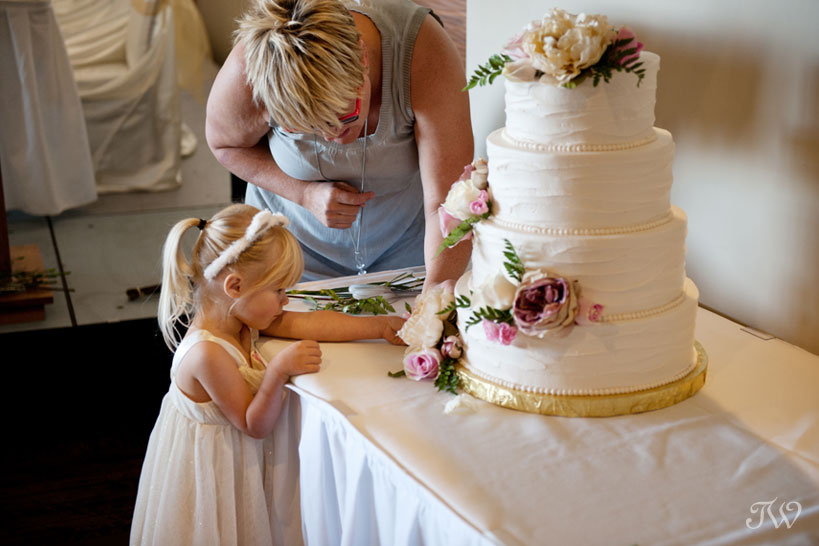 Cakeworks putting the final touches on a wedding cake captured by Tara Whittaker Photography