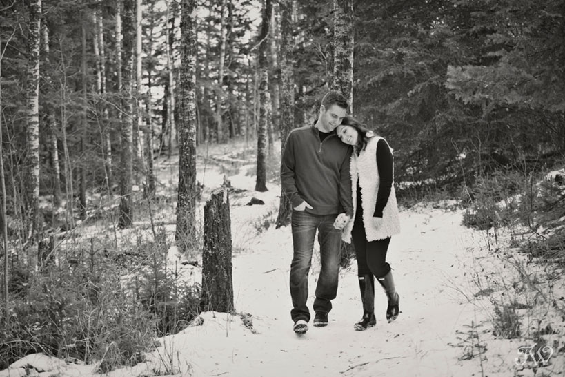 couple stroll in the woods during their winter engagement session captured by Tara Whittaker Photography