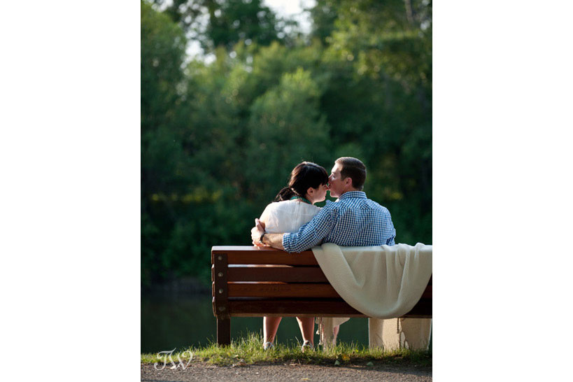 couple kiss on a park bench during their summer engagement session captured by Tara Whittaker Photography