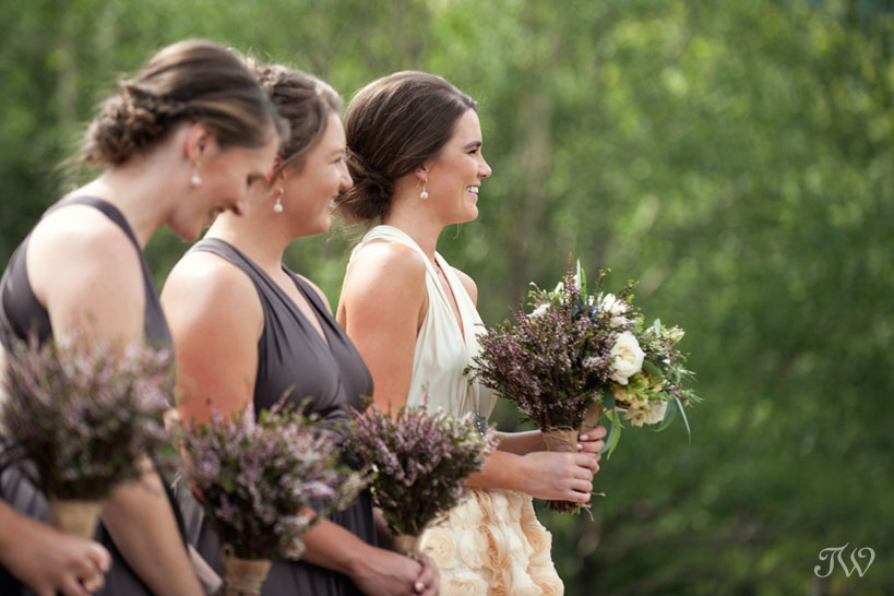 bridesmaids laugh during ceremony captured by Calgary wedding photographer Tara Whittaker