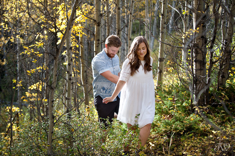 bride and groom walk through the woods during their fall engagement session