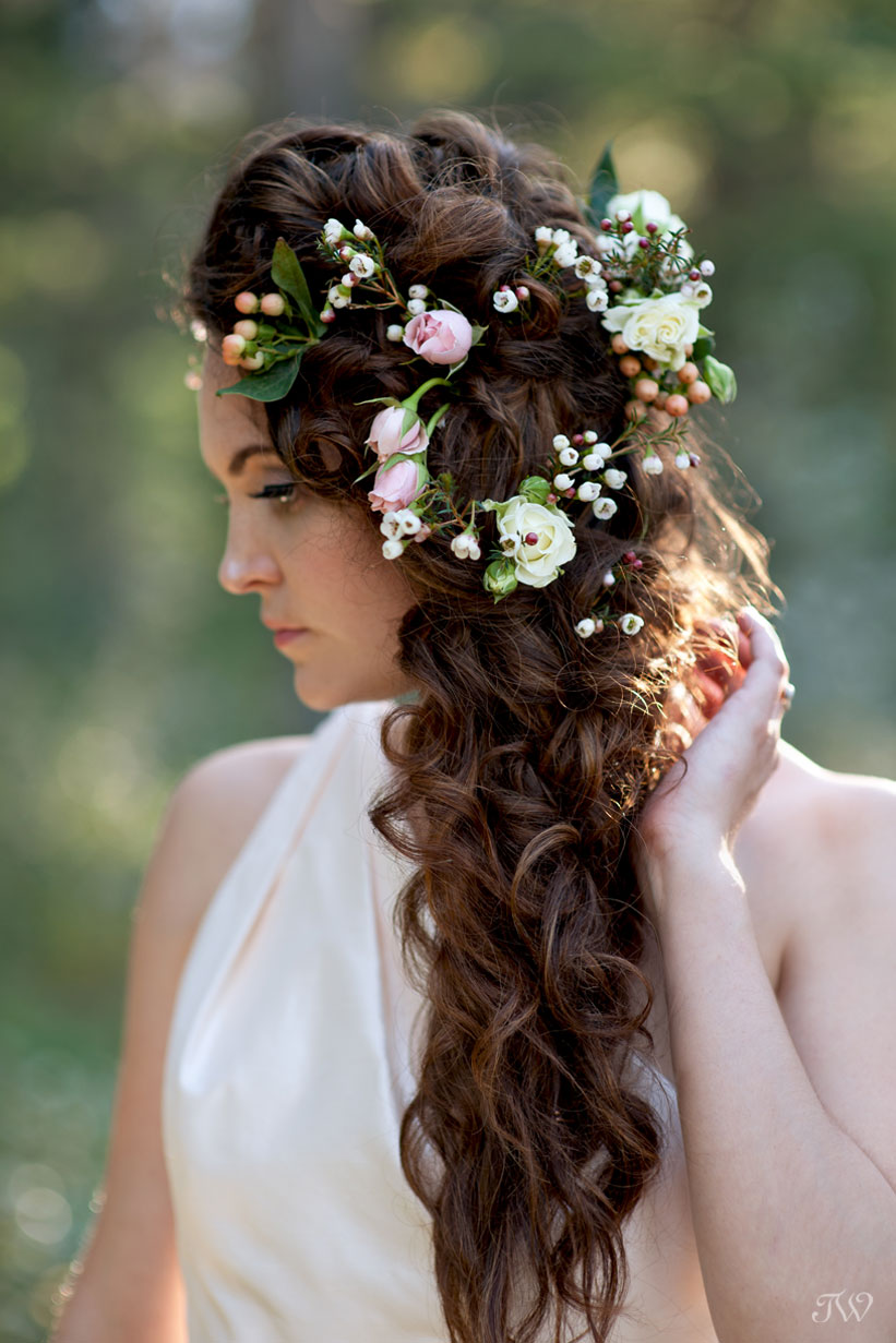 Rocky Mountain bride wears flowers in her hair captured by Calgary wedding photographer Tara Whittaker