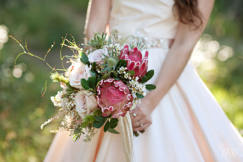 Rocky Mountain bride carries a bouquet of pink protea captured by Calgary wedding photographer Tara Whittaker