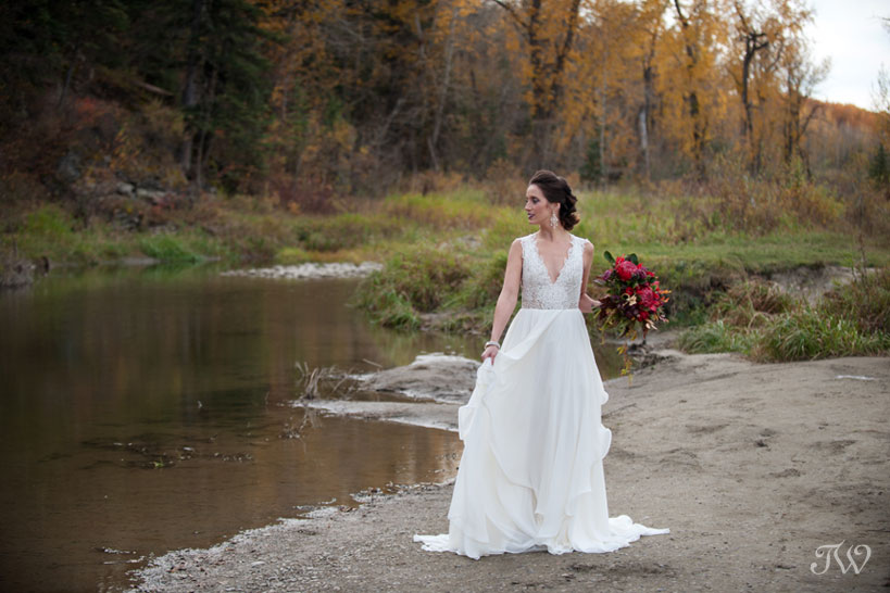 fall bride on river bank wearing Hayley Paige bridal captured by Calgary wedding photographer Tara Whittaker