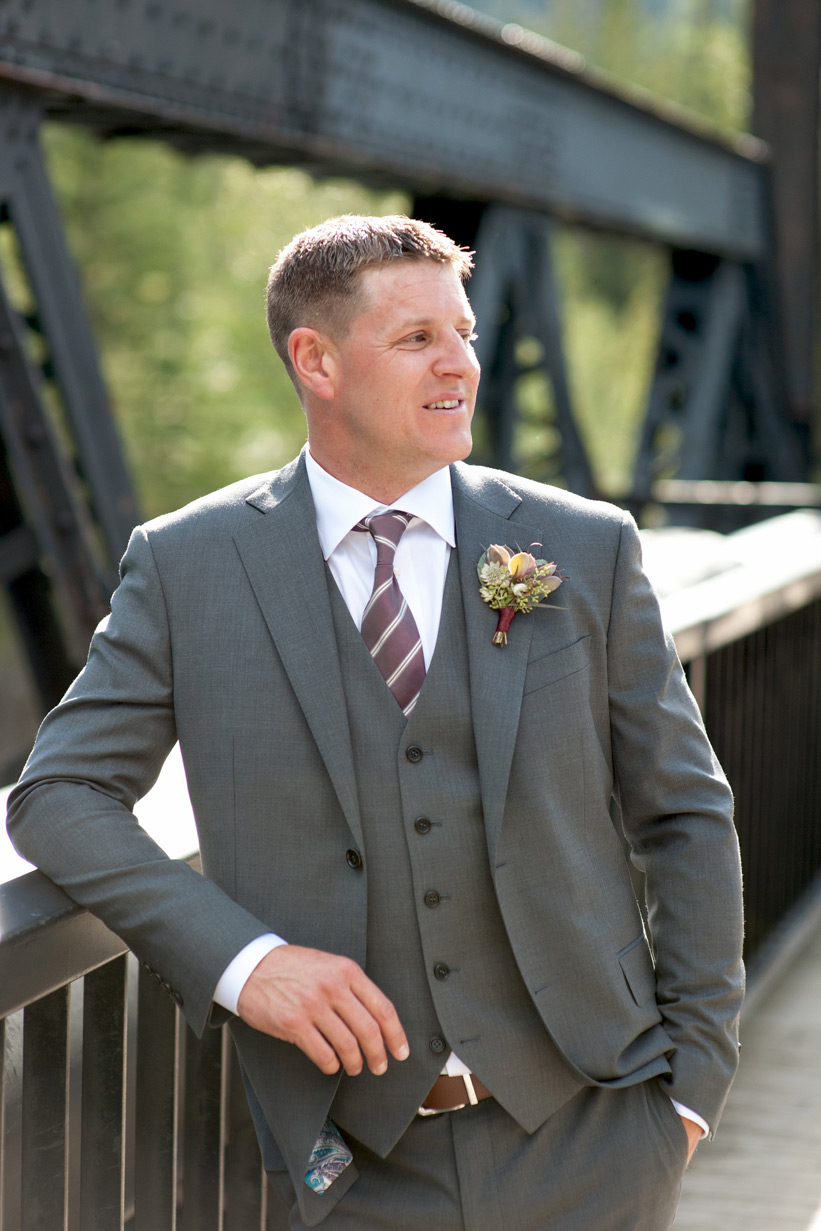 groom on the railway bridge in Canmore captured by Tara Whittaker Photography