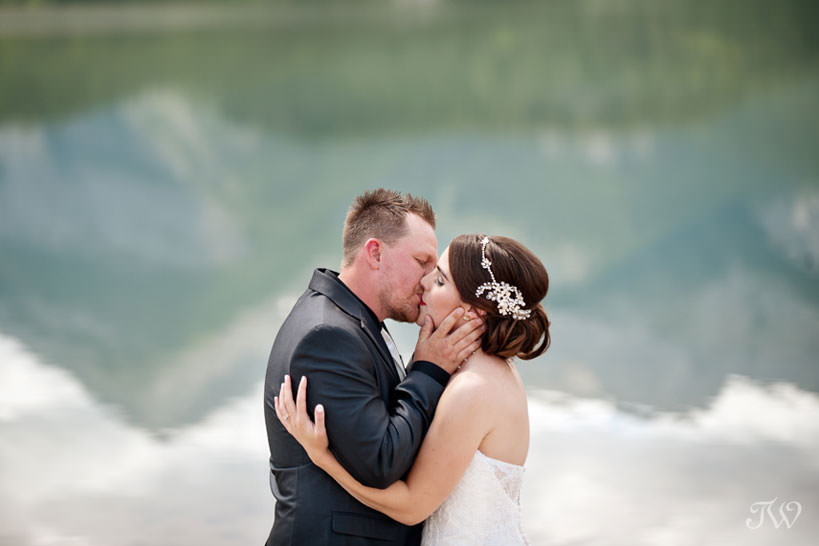 First kiss on the shore of Barrier Lake captured by Calgary wedding photographer Tara Whittaker