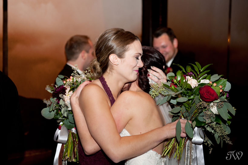 bride embraces her bridesmaid captured by Calgary wedding photographer Tara Whittaker