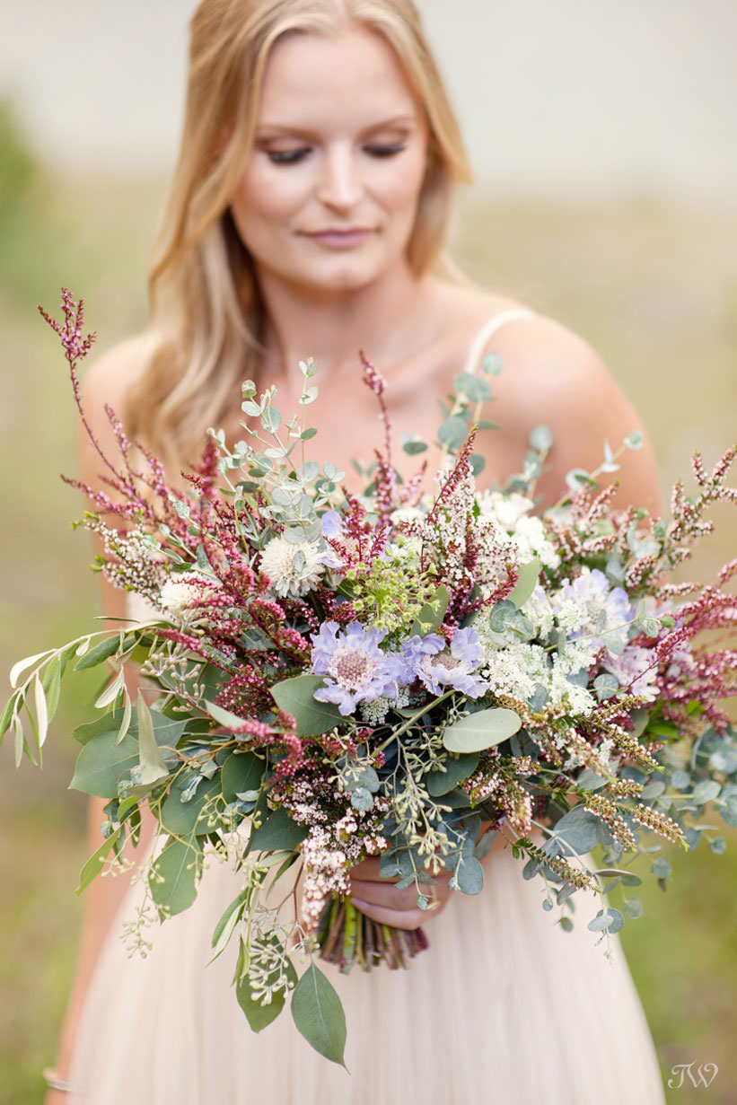 Caitie carries a wildflowers bouquet at her Spray Lakes engagement session captured by Tara Whittaker Photography