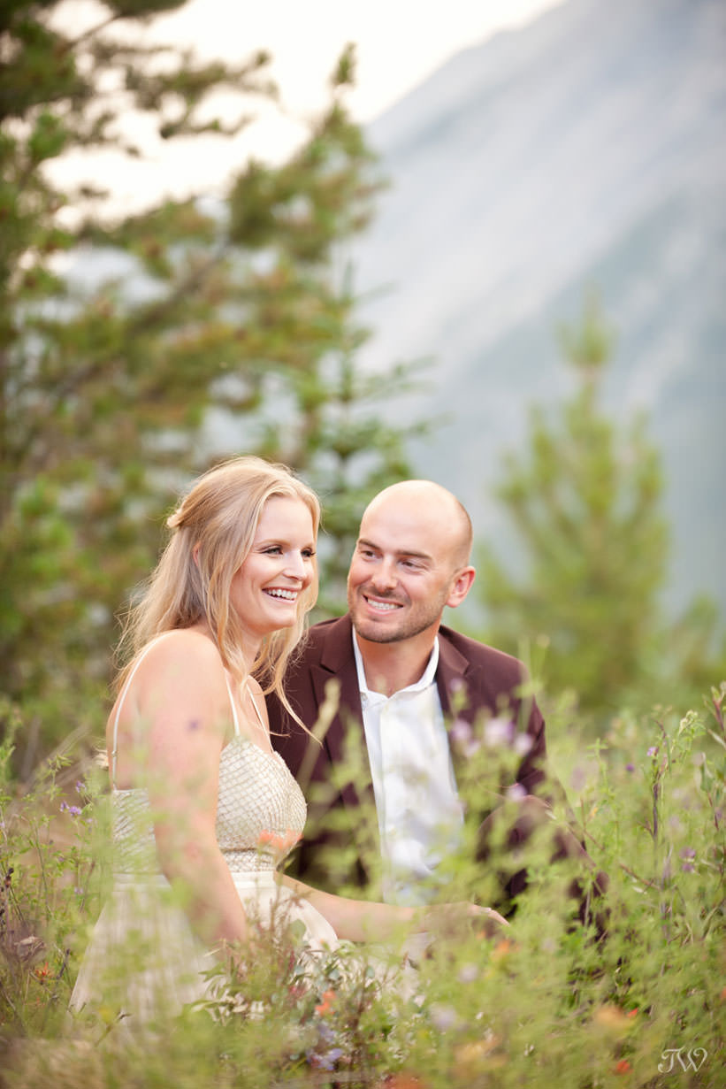 Couple sit in the wildflowers at their Spray Lakes engagement session captured by Tara Whittaker Photography