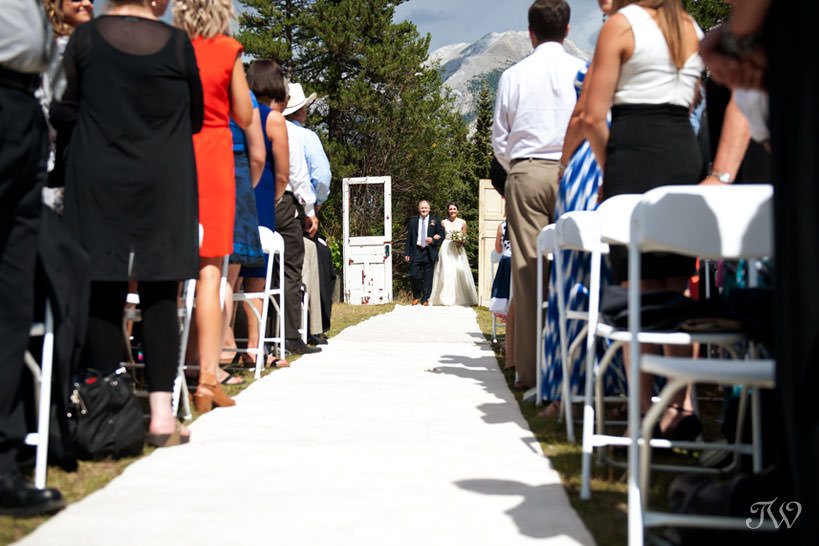 Canmore bride walks down the aisle with her Dad captured by Tara Whittaker Photography