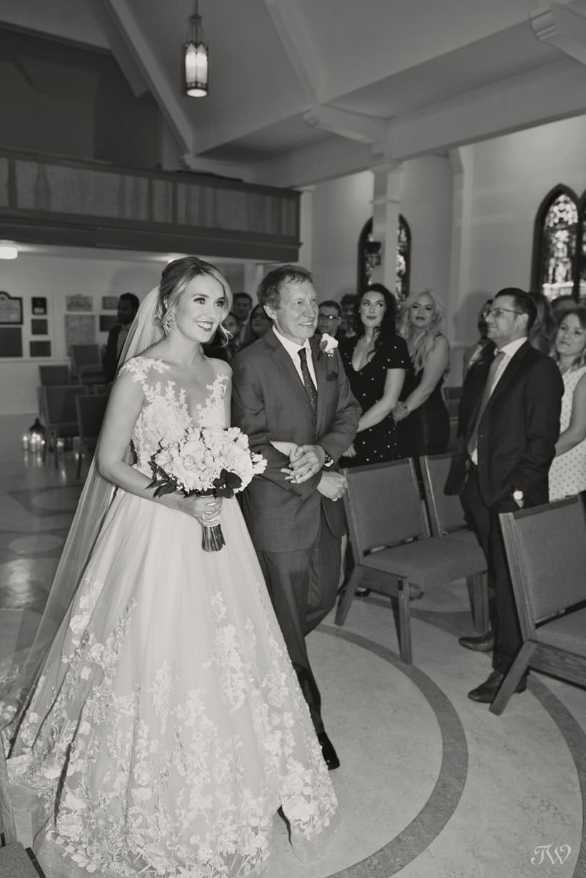 Bride walks down the aisle at St Stephen's Church captured by Calgary wedding photographer Tara Whittaker