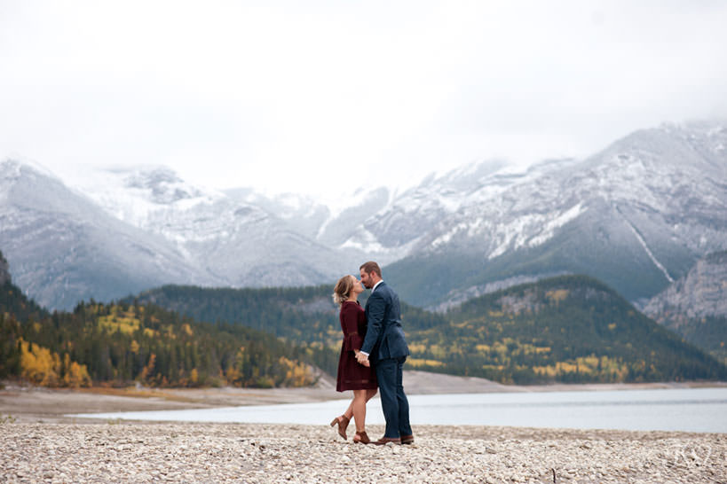 bride and groom share a kiss on the shore of Barrier Lake in Kananaskis captured by Tara Whittaker Photography
